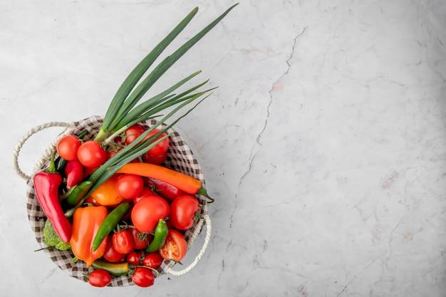 白い表面の左側にネギトマトピーマンとして野菜がいっぱい入ったかごの上から見る