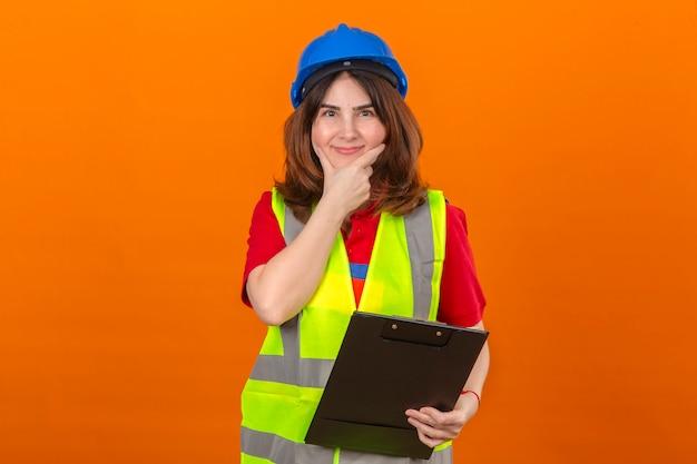 孤立したオレンジ色の壁を選択する顔に笑顔であごの思考に触れるクリップボードを手に保持している建設ベストと安全ヘルメットを身に着けている女性エンジニア