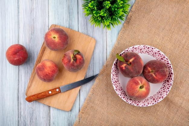ナイフと木製キッチンボード上の桃と灰色の表面の袋布の皿に桃