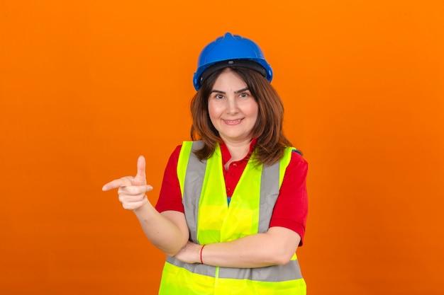 分離のオレンジ色の壁の上に立っている顔に笑顔で何かを指している建設ベストと安全ヘルメットを身に着けている女性エンジニア