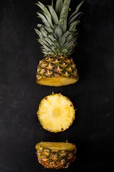 Вид сверху нарезанный ананас на черной поверхности