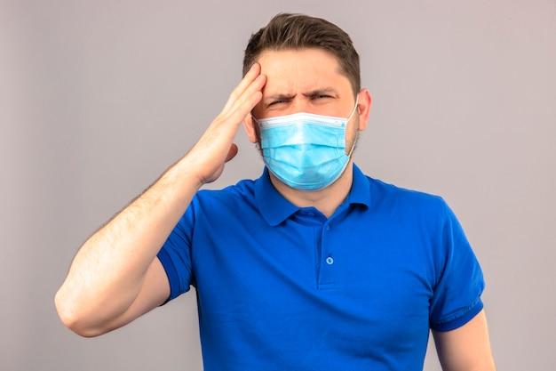 孤立した白い壁に頭痛に苦しんでいる頭の上の手で体調不良と病気の立っている探している医療用防護マスクで青いポロシャツを着ている若い男