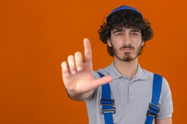 若いひげを生やしたハンサムなビルダー身に着けている建設ユニフォームとキャップを指で指していると怒っている式は孤立したオレンジ色の壁にジェスチャーを示さない