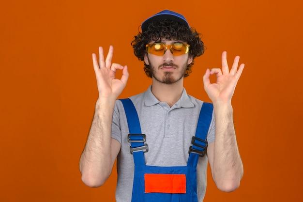 若いハンサムなビルダーひげを生やした建設ユニフォームメガネとキャップを身に着けてリラックスして目を閉じて笑顔孤立したオレンジ色の壁に指で瞑想ジェスチャーをして