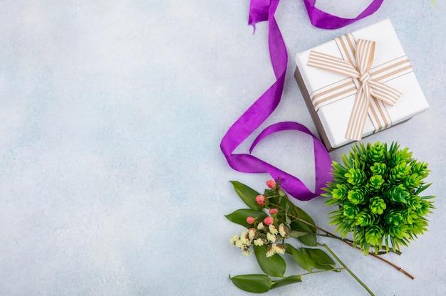 Взгляд сверху розовых ягод зверобоя с подарочной коробкой на белой поверхности