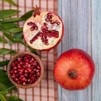 格子縞の布の上の葉と木製の表面の上全体とザクロ半分とザクロ果実のボウルの平面図