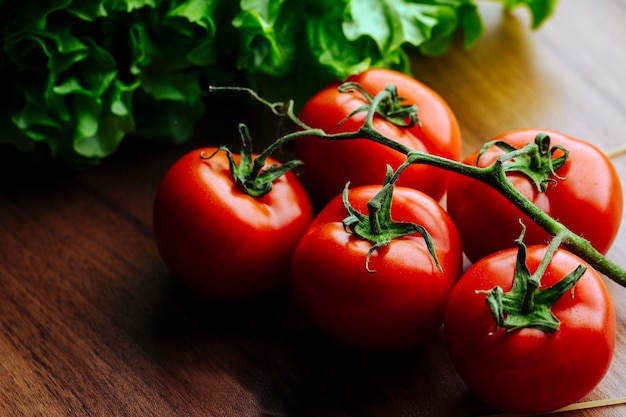 Целые помидоры на деревянной поверхности