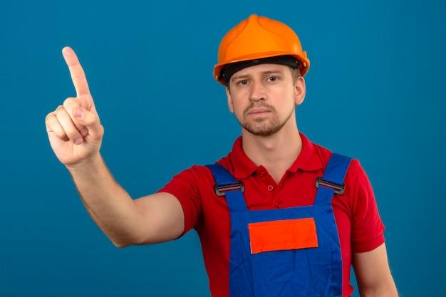 孤立した青い壁に深刻な顔を指で上向き建設制服と安全ヘルメットの若いビルダー男