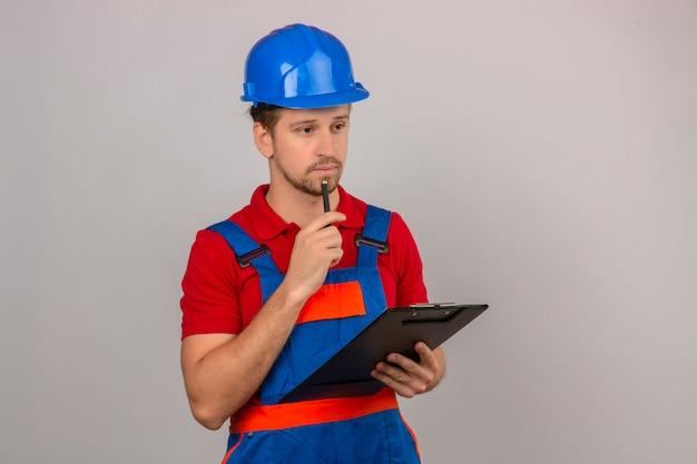 Молодой строитель человек в строительной форме и защитный шлем, стоя с буфером обмена в руке и касаясь подбородка с ручкой с серьезным лицом на изолированной белой стене