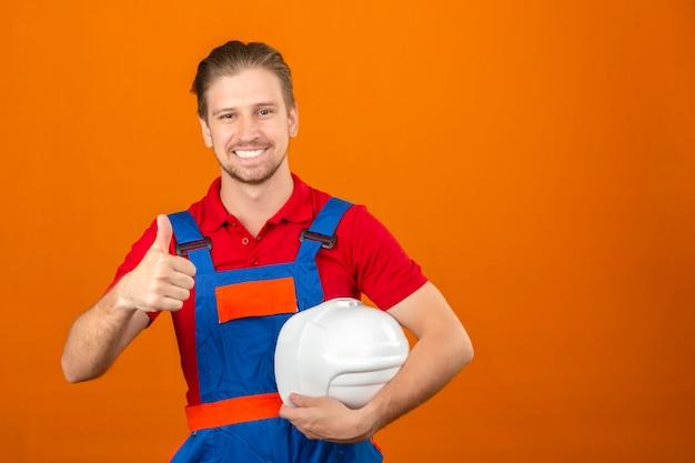 安全ヘルメットを手で押し、コピースペースを持つ孤立したオレンジ色の壁を越えて立っている顔に大きな笑顔で親指を現して建設制服を着た若いビルダー男