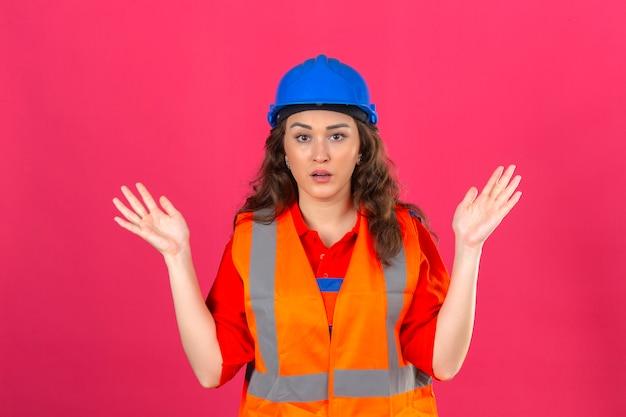 Молодая женщина строитель в униформе конструкции и шлеме безопасности невежественный и смущенный с руками и руками поднял концепцию сомнения над изолированной розовой стеной