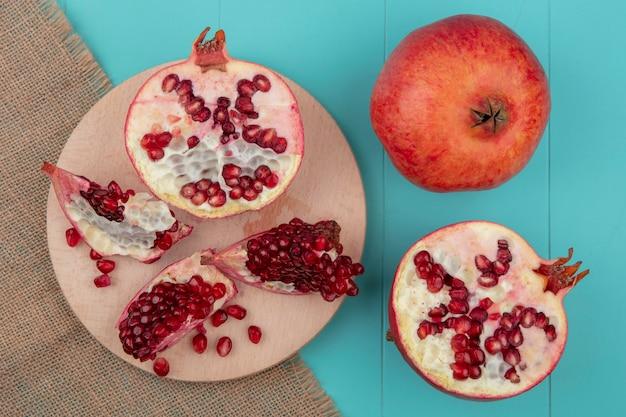 ザクロの部分とザクロの半分果実と青い表面に荒布をまな板の上の果実と半分の上から見る
