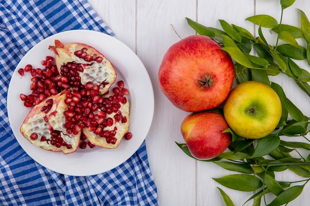 Вид сверху кусочки граната в тарелке на клетчатой ткани и целое одно яблоко сливы с листьями на деревянной поверхности