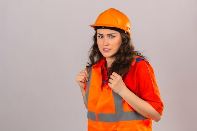 Молодая женщина строитель в строительной форме и защитный шлем нахмурившись с выражением лица сомнение скептицизм над изолированной белой стеной