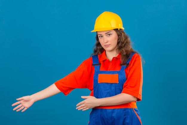 Молодая женщина строитель в строительной форме и защитный шлем, представляя и указывая ладонями рук, глядя на камеру с серьезным лицом на изолированной синей стене