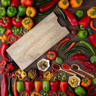Овощи и разделочная доска на бордовом столе