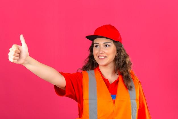 Молодая женщина строитель в строительной форме и защитный шлем, показывает палец вверх, чтобы кто-то улыбается дружелюбно над изолированных розовые стены