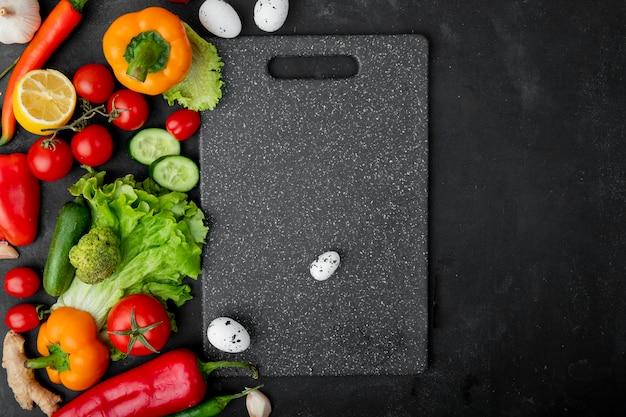 あずき色のテーブルにまな板と野菜