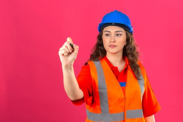 Молодой строитель женщина в строительной форме и защитный шлем постоянный написание в воздухе с ручкой над изолированной розовой стеной