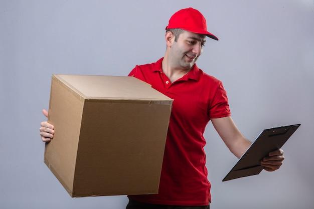 Молодой доставщик в красной рубашке поло и кепке держит картонную коробку и смотрит в буфер обмена в другой руке с улыбкой на положительном лице на изолированной белой стене