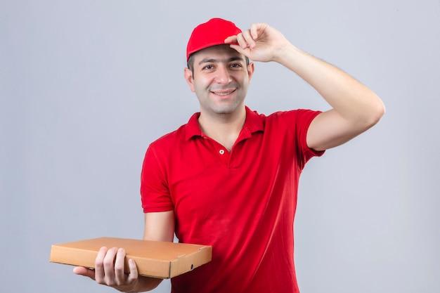 赤いポロシャツとピザの箱を持って若い配達人が挨拶のジェスチャーを作るピザの箱を押しながら分離の白い壁に優しい笑みを浮かべて彼の帽子に触れる