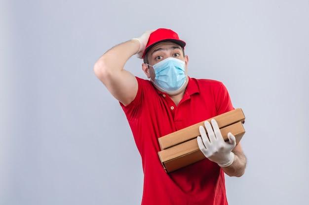 赤いポロシャツの若い配達人とピザの箱を保持している医療用マスクのキャップ分離の白い壁を間違えて頭に手でイライラ