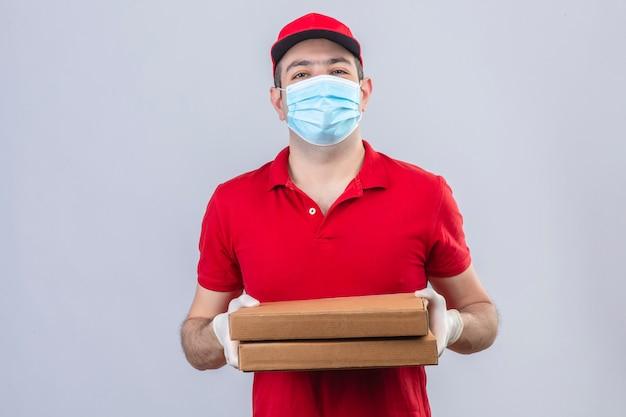 赤いポロシャツの若い配達人と分離の白い壁の上の顔に笑顔でピザの箱を保持している医療マスクのキャップ