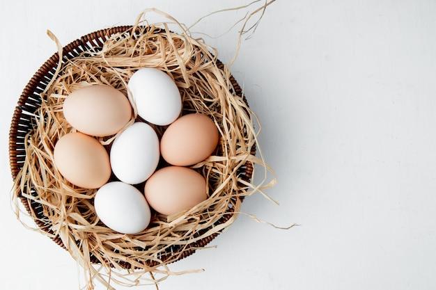 白いテーブルの上の巣に卵がいっぱい入ったかご