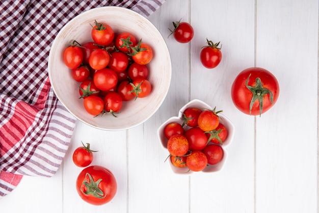 ボウルに格子縞の布と木の表面にトマトのトップビュー