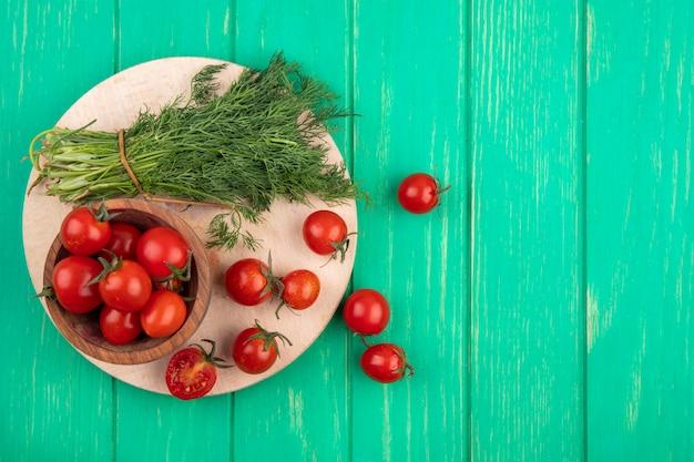 緑の表面にまな板の上のトマトのボウルとディルの束として野菜のトップビュー