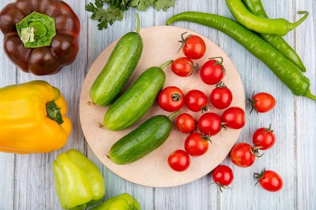 木製の表面にコショウでまな板の上のキュウリトマトとして野菜のトップビュー