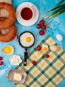 Жареное яйцо, чай и помидор на синем столе