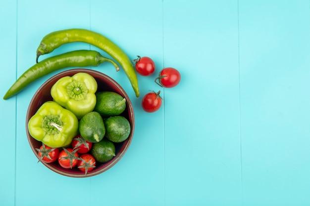 Вид сверху овощей как перец огурец помидор в миску и на синей поверхности
