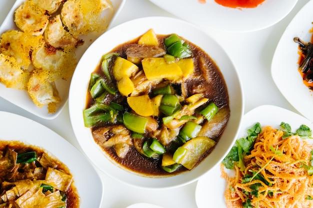 Китайский суп с мясом, овощами и зеленым перцем в тарелке