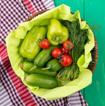 格子縞の布と緑の表面にバスケットのペッパートマトキュウリディルとして野菜のトップビュー