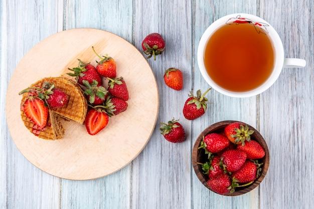 まな板の上のワッフルビスケットと木製の表面にお茶のカップをボウルにイチゴのトップビュー