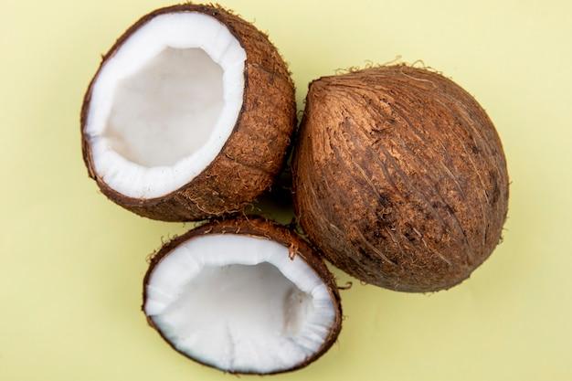 黄色の表面に全体と半分の大きなココナッツの平面図