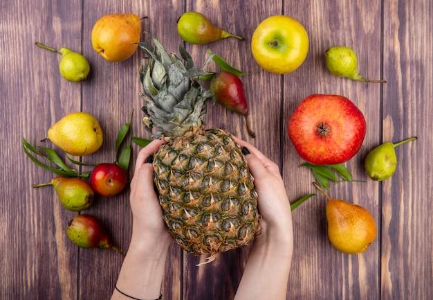 Взгляд сверху рук женщины держа ананас с гранатовым деревом сливы яблока персика на деревянной поверхности