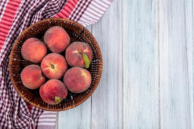 Вид сверху сочные и вкусные персики на ведре на проверенной скатерти на серой деревянной поверхности