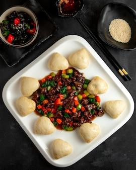 Жареное мясо и овощи и манту на тарелке