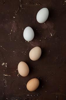 Белые и коричневые яйца на бордовом столе