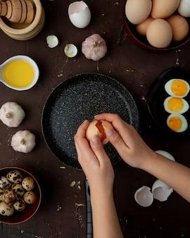 マルーンテーブルにバターガーリックとしてフライパンと食品に開いた卵を割る女性の手
