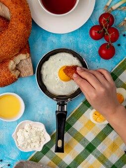 Женская рука ест хлеб с жареным яйцом