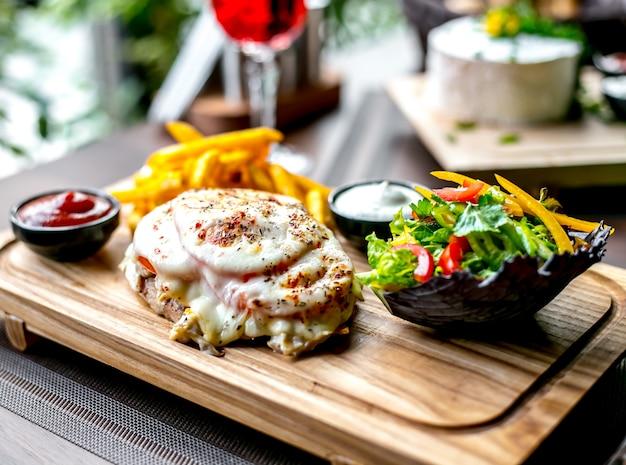 Жареная куриная грудка с сыром, помидорами, картофелем фри, кетчупом и зеленым салатом