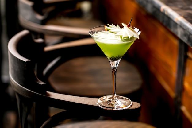 Коктейль из киви в бокале для мартини, украшенный кусочками яблок на бамбуковой шпажке