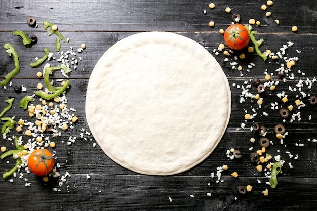 Тесто для пиццы рядом с сыром окропляет оливковое зерно помидор и перец на черном фоне деревянные