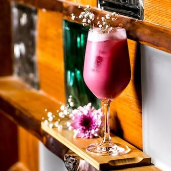 長いスタンドグラスにカスミソウを添えた紫のカクテル