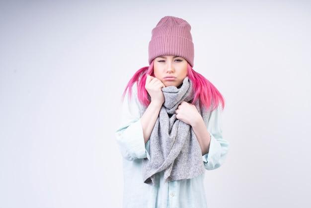 Замерзшая девушка с шарфом и розовой шляпой