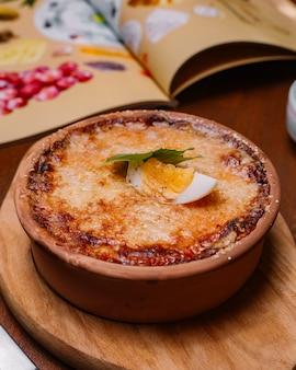 Жареное итальянское блюдо в кастрюле, украшенное плавленым сыром и половиной вареного яйца