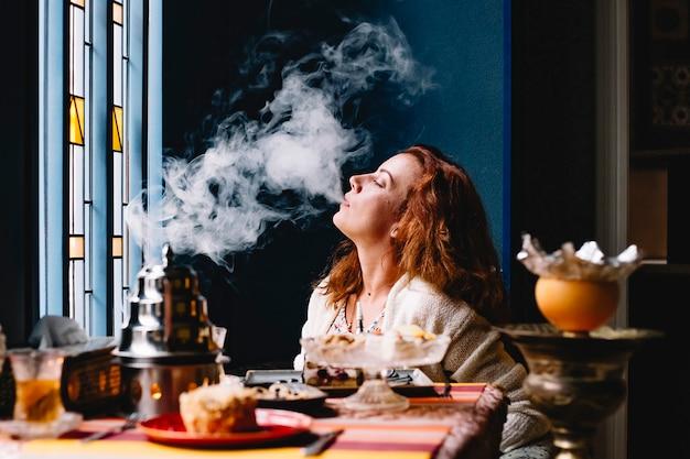 Женщина выдувает дым из кальяна в ресторане